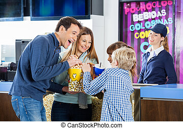 Playful Family Enjoying Snacks At Cinema Concession Stand