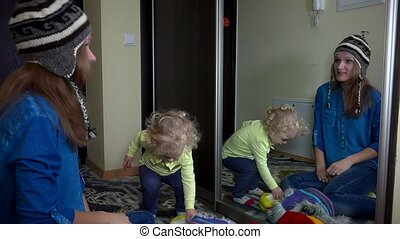 Playful family girls measuring warm winter hats near mirror