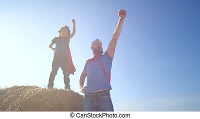 Serious dad and son playing superheroes while stretching clenched fist forward and up. Little boy standing on straw stack near father during play on background of blue sky