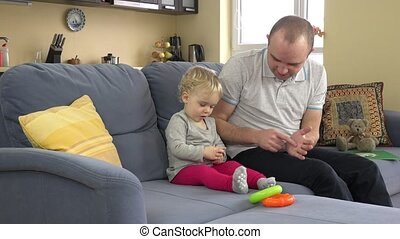 playful father have fun with baby girl on sofa at home. Man tickle toddler girl