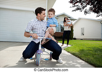 Playful Father Sitting on Tricycle With Son