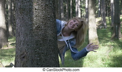 Playful funny smiling teenage woman having fun in the forest...