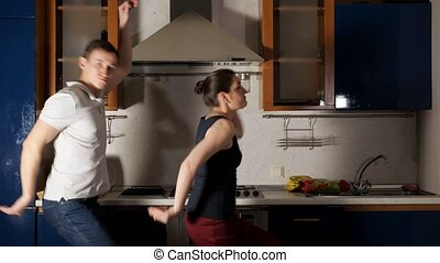 playful girl and guy dance and grimace having fun and walking along kitchen with modern equipment close view