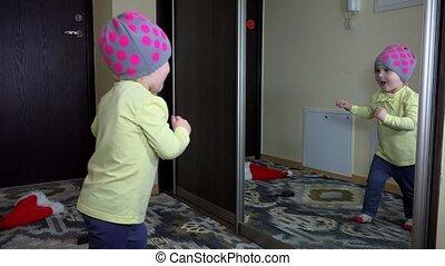 Playful girl kissing herself in mirror on cabinet door