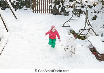 Playful girl running, playing in home backyard