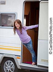 Playful Girl Standing At Caravan Entrance - Portrait of...