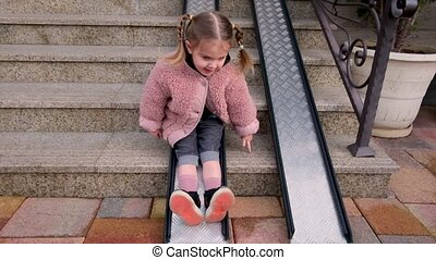 Playful girl with plaits slides down metal ramp on steps