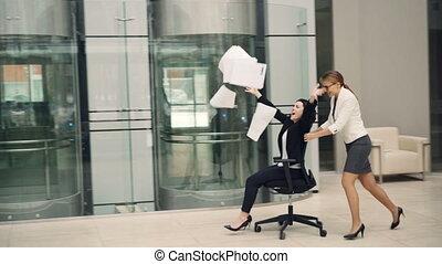 Playful girls businesswomen are having fun in office lobby...