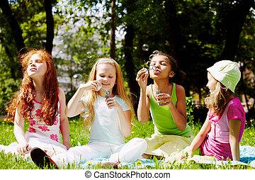 Playful girls - Portrait of cute girls having fun on green...