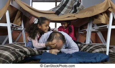 Playful granddaughters tickling their grandfather - Playful...