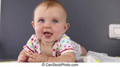 Playful grimacing baby on plaid - Adorable grimacing funny...