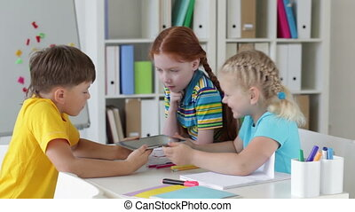 Group of schoolchildren playing with a touchpad during the break