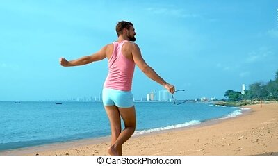 Playful handsome guy in a pink t-shirt and blue shorts...