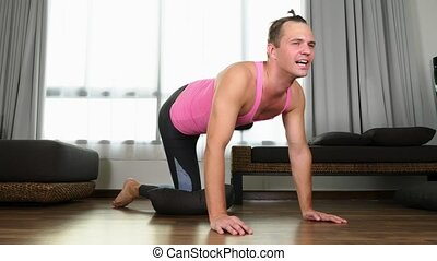 Playful handsome guy in a pink t-shirt engaged in fitness,...
