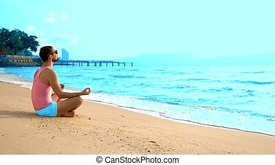 Playful handsome man in pink t-shirt and blue shorts meditates while sitting by the sea