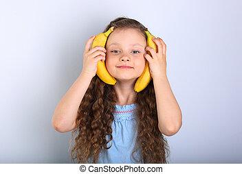 Playful happy fun long hair kid girl holding yellow bright...