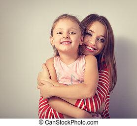 Playful happy mother hugging her joking grimacing kid with love. Toned closeup portrait