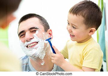 playful kid and dad shaving together at home bathroom