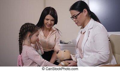 Playful kid patient using stethoscope in clinic - Joyful ...