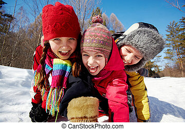 Playful kids - Happy friends in winterwear looking at camera...