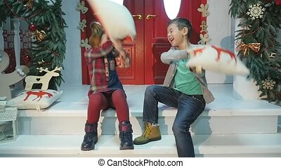 Playful kids having pillow fight. New year concept