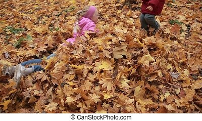 Playful kids lying in pile of yellow foliage