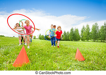 Playful kids throwing colorful hoops on cones while ...