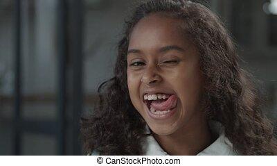 Playful little black girl making funny grimaces
