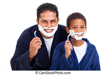 playful little boy shaving with father