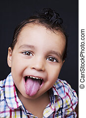 Playful little boy sticking out his tongue with smiling eyes