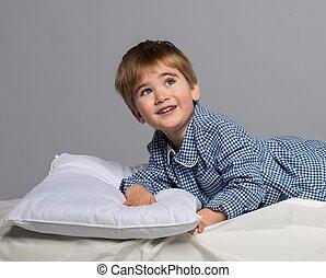 Playful little boy wearing blue pajamas in bed