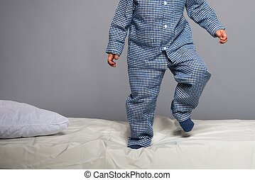 Playful little boy wearing blue pajamas in bed