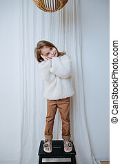 Playful little girl in sweater is standing on a stool, making sleep gesture