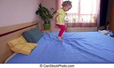 Playful little girl kid jump and run on bedroom bed