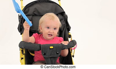 Playful Little Girl Sitting In Pram And Playing With Toy Spade
