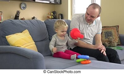 playful little sweet girl paly with father on sofa in room. 4K