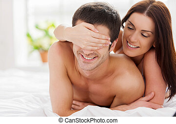 Playful loving couple. Cheerful young loving couple lying in...