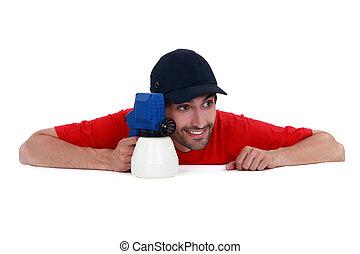 Playful man holding a spray gun
