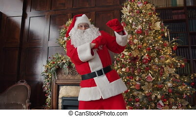 Playful man in Santa Claus costume dancing indoors near Christmas tree