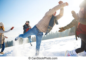 Playful man with crew on the snow