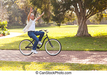 playful middle aged man riding a bike outdoors with arms up