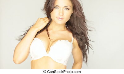Playful Model Accentuating Breasts by throwing her arms back and chest forwards, wearing a bra.