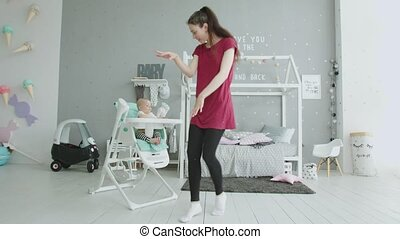 Playful mom entertaining baby sitting in highchair