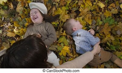 Playful mom tickling happy little children in park
