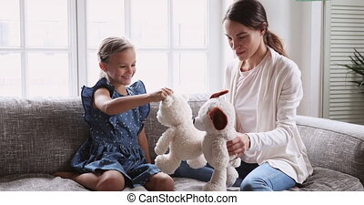 Playful mommy babysitter and kid daughter playing stuffed toys