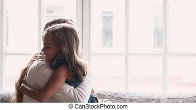 Playful mother and cute child daughter playing hugging on sofa