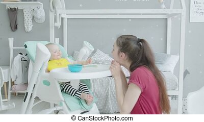 Playful mother making baby laugh during feeding