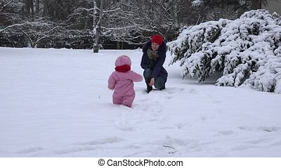 Playful mother with dummy attract baby child to walk on snow in winter. 4K