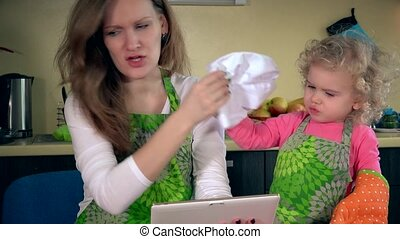 Playful mother with little helper have fun in kitchen with tablet computer