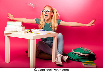 Playful, naughty schoolgirl with big eyeglasses playing with paper aeroplane while should study.